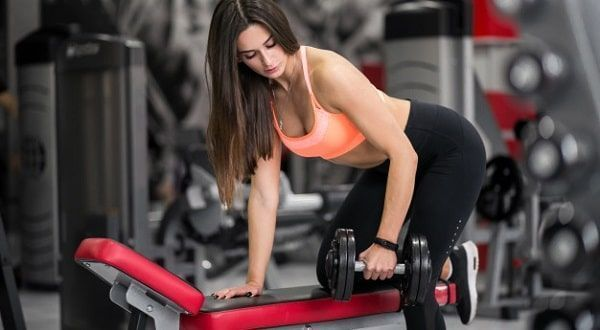 Chica apoyándose en banco para pesas