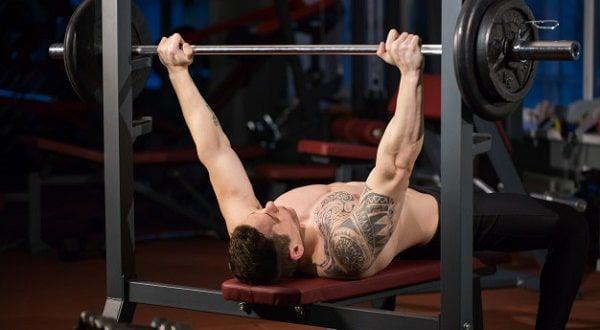 Hombre alzando barra acostado en banco para pesas