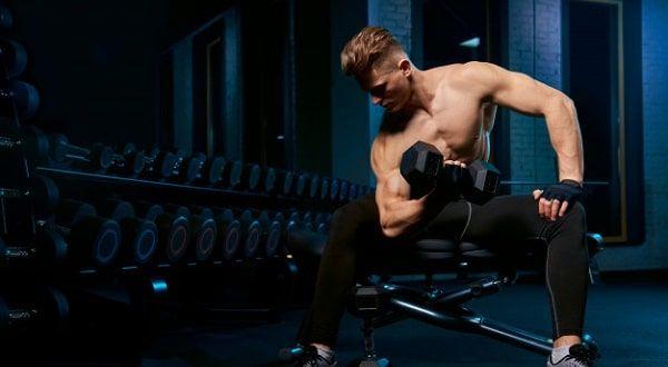 Hombre sentado en banco para pesas