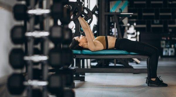 Mujer acostada en banco para pesas
