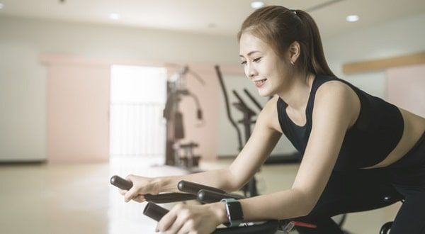 Mujer joven entrenando bicicleta gimnasio