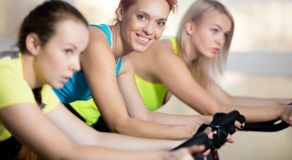 Mujeres usando bicicleta de gimnasio