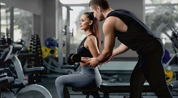 Personas usando banco para pesas