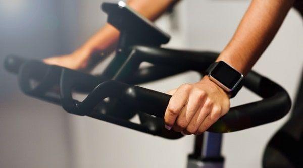 Mujer agarrando mango de bicicleta de gimnasio