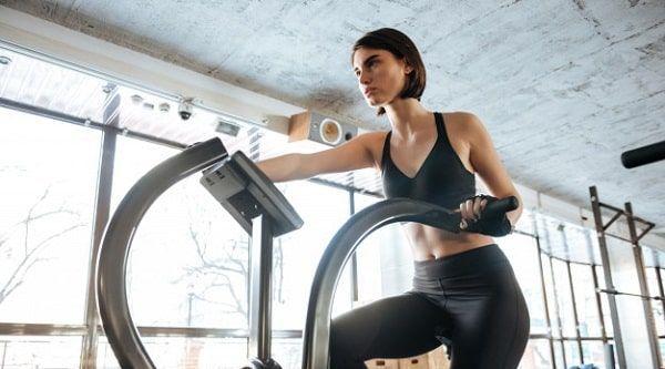 Mujer joven en bicicleta de gimnasio