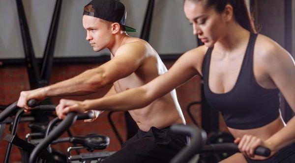 pareja joven en bicicleta de gimnasio