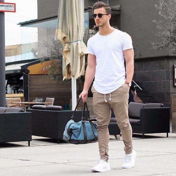 hombre con joggers beige y camiseta blanca por la calle